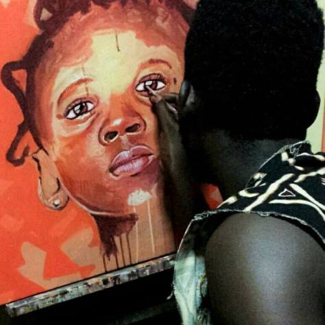 Kwesi Botchway at work in his studio on portrait of young girl
