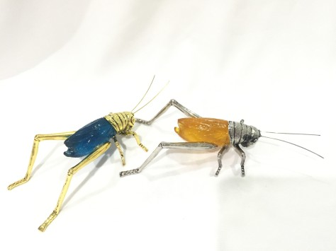 gold feng shui cricket paired with a silver feng shui cricket